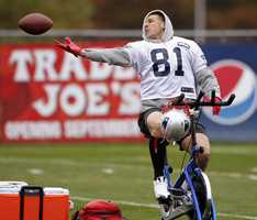 New England Patriots tight end Aaron Hernandez (81) can not hang onto the ball as he tries to catch a pass while riding a stationary bike during practice at the NFL football team's facility in Foxborough, Mass., Wednesday, Oct. 24, 2012.