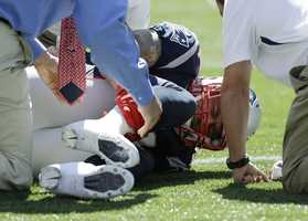 New England Patriots tight end Aaron Hernandez holds his right lower leg as he lies on the field in the first quarter of an NFL football game against the Arizona Cardinals, Sunday, Sept. 16, 2012, in Foxborough, Mass.