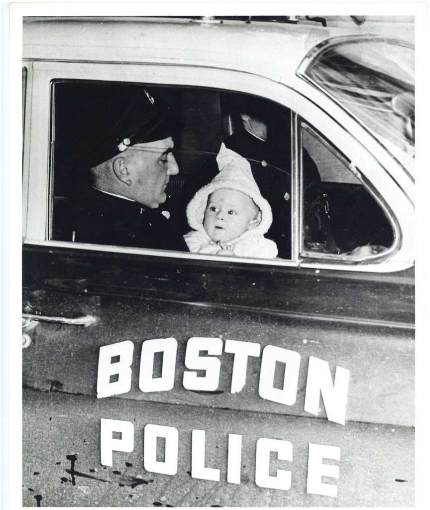 A displaced child sits in a Boston police cruiser.