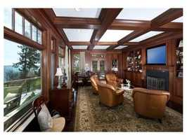 The den has a wood burning fireplace, dark rich floors, raised panel walls, and coffered ceiling.