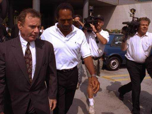 O.J. Simpson, center, and his attorney Howard Weitzman, right, are besieged by the media as they leave police headquarters in downtown Los Angeles, June 13, 1994, after Simpson was questioned in connection with the murders of his ex-wife Nicole Brown Simpson and Ronald Lyle Goldman, 26, at the woman's Los Angeles condominium.