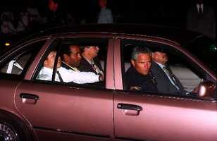 Simpson surrendered after demanding that he be allowed to speak to his mother. Simpson, center of rear seat, rides into Parker Center, the Los Angeles Police Department headquarters, Friday night, June 17, 1994.