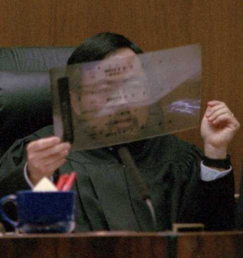 Superior Court Judge Lance Ito holds up a sample of an autoradiology picture of DNA sequences during the trial. Two attorneys specializing in DNA evidence were hired by the defense to discredit the prosecution's DNA evidence.