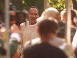 O.J. Simpson smiles during the taping of a video in the driveway at his Brentwood estate, Dec. 21, 1995, in Los Angeles. In remarks to his own video crew, Simpson declared his innocence in the murders of his ex-wife and her friend. He criticized DNA blood evidence and a prosecutor involved in his murder trial.