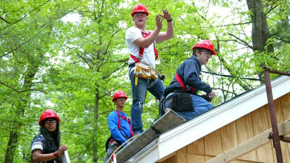 Students from the Greater Lowell Technical High School work on a cabin-building project at Camp Massapoag in Dunstable, Mass., Thursday, May 21, 2014.
