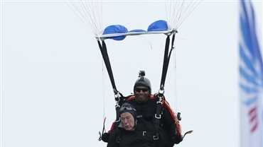 Former President George H.W. Bush, strapped to Sgt. 1st Class Mike Elliott, a retired member of the Army's Golden Knights parachute team, prepare to land on the lawn at St. Anne's Episcopal Church while celebrating Bush's 90th birthday in Kennebunkport, Maine, Thursday, June 12, 2014.