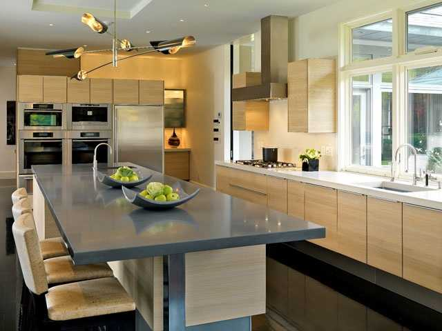 The kitchen, featuring oak cabinets by Poggenpohl and quartz countertops, has two Miele ovens, a 42-inch gas Miele Master Chef cook top, a 30-inch full size Sub-Zero refrigerator and large kitchen island with refrigerator and freezer drawers.