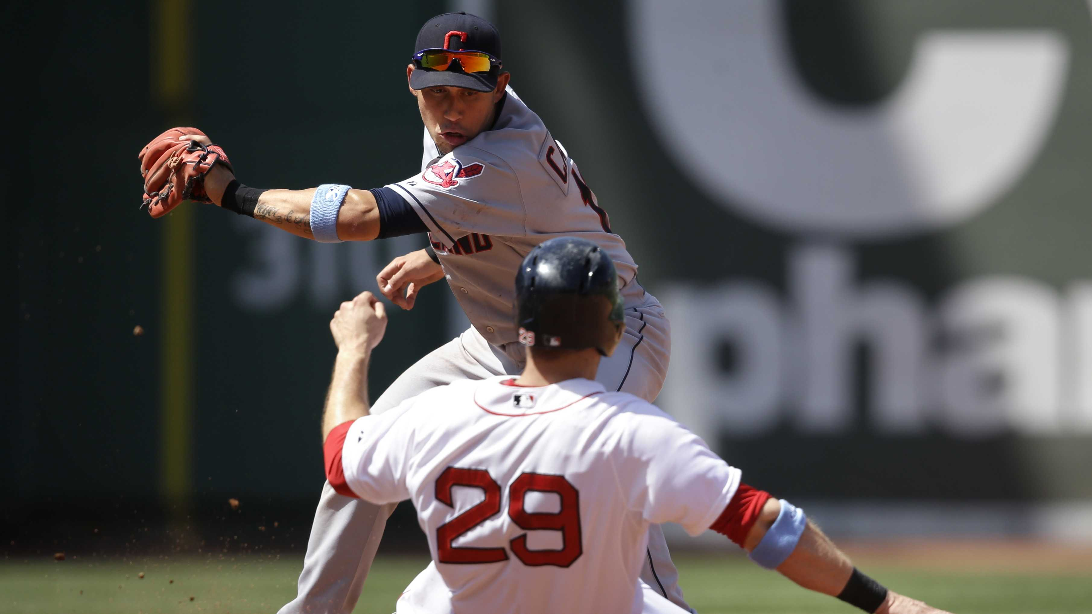 Boston Red Sox's Daniel Nava (29) slides out on a steal attempt as Cleveland Indians shortstop Asdrubal Cabrera, top, tags him in the fourth inning of a baseball game, Sunday, June 15, 2014, in Boston. (AP Photo/Steven Senne)