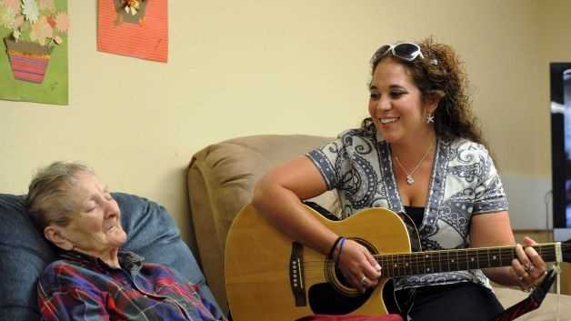 "Brianna LePage, right, sings ""Edelweiss"" to Erika Groth who participates in The Gathering Place. LePage was trained in music therapy. She now uses her skills as a singer and musician to help those with dementia access their memory."