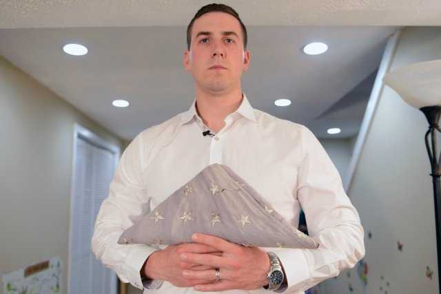 In his home in New Hampshire, May 3, 2014, Ryan Pitts, who is to receive the Medal of Honor for combat actions in Afghanistan, holds the flag that his grandfather flew every day while Pitts served in the Army.