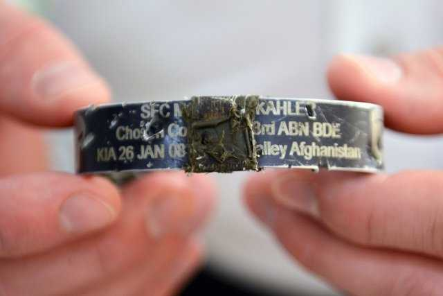 In his New Hampshire home, May 3, 2014, Ryan Pitts holds the KIA bracelet he was wearing the time of the attack in Wanat. The bracelet honors Sgt. 1st Class Matthew Kahler, who died Jan. 26, 2008 after being shot by an Afghan guard.