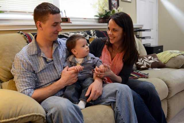 Ryan Pitts and his wife Amy share a moment with their son Lucas, at their home in New Hampshire, May 3, 2014.