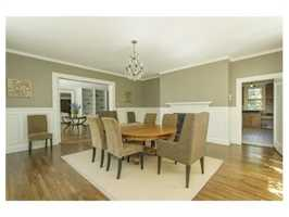 The inviting dining room has a lovely fireplace, wainscoting, and bay.