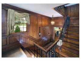 Entering the home you will be welcomed into a dramatic wood paneled entry hall.