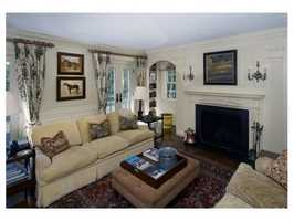 The adjacent stunning family room has original moldings and a fireplace.