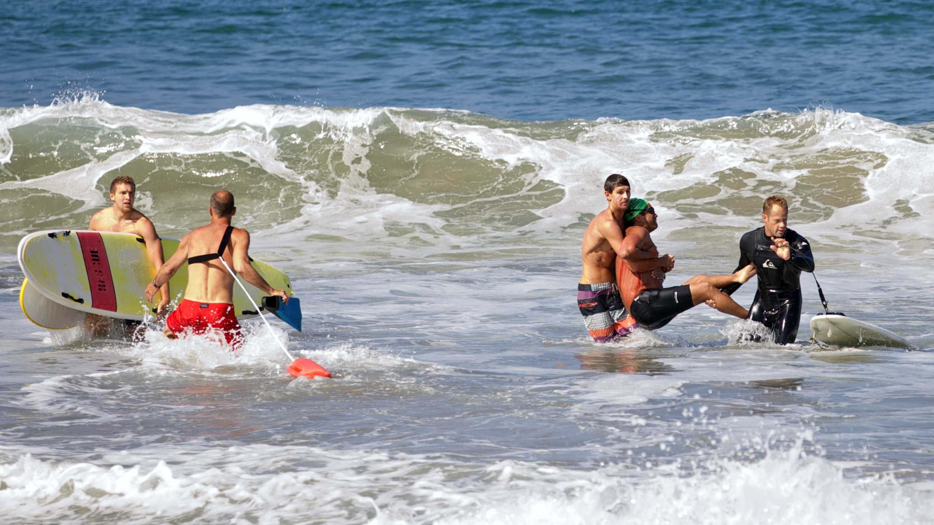 In this photo by Laura Joyce of goofyfootphotography.com, two men carry a swimmer, second from right, after he was bitten by a great white shark, as lifeguards close in at left in the ocean off Southern California's Manhattan Beach, Saturday, July 5, 2014. The man, who was with a group of long-distance swimmers when he swam into a fishing line, was bitten on a side of his rib cage according to Rick Flores, a Los Angeles County Fire Department spokesman. The man's injuries were not life-threatening and he was taken to a hospital conscious and breathing on his own, Flores said.