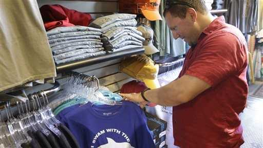 Vacationer Mark McCurdy, of Everett, Mass., examines shark-themed clothing at the Chatham Clothing Bar in Chatham, Mass. Growing sightings of great white sharks off Cape Cod are generating business for local entrepreneurs as residents and tourists seek a glimpse of the offshore predators -- or purchase their shark-themed memorabilia and apparel.