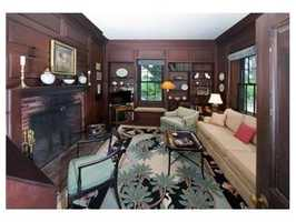 Ahandsome wood paneled library with fireplace.