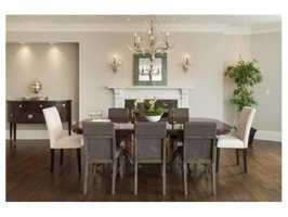 A banquet sized formal living & dining room has dual gas fireplaces, enormous windows along a curved wall, stately moldings, and white oak floors.