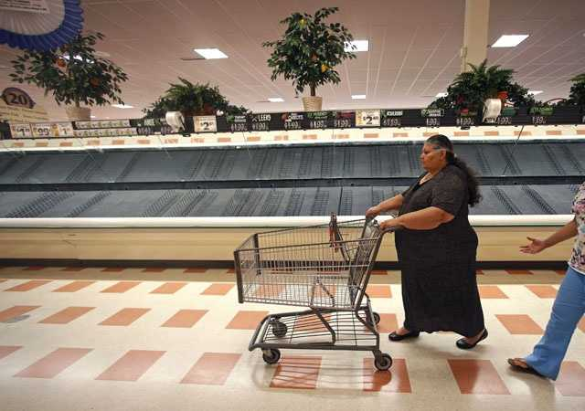 Maria Arvarado, of Haverhill, Mass. finds empty produce bins as she shops at Market Basket in Haverhill, Thursday, July 24, 2014.