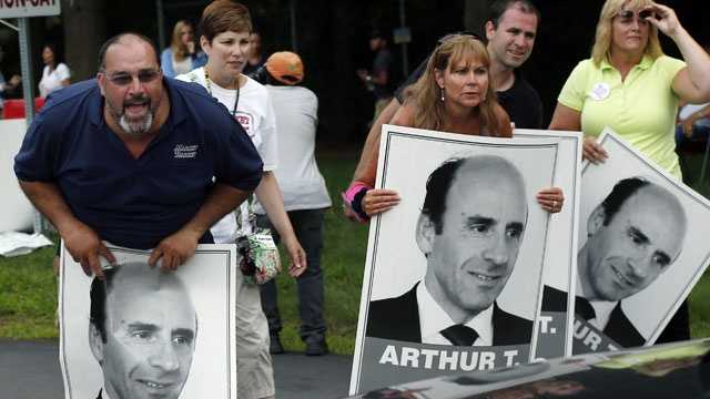 "Protesters holding ""Arthur T"" signs taunt an occupant of a car driving from a Market Basket Supermarket job fair in Andover, Mass., Monday, Aug. 4, 2014."