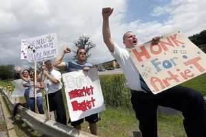 Market Basket employees acknowledge passing supporters as they picket in front of the store in North Andover, Mass., Thursday, July 24, 2014.