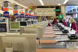 Cashiers and baggers stand idle Thursday July 24, 2014 at a Market Basket supermarket in Concord, N.H.