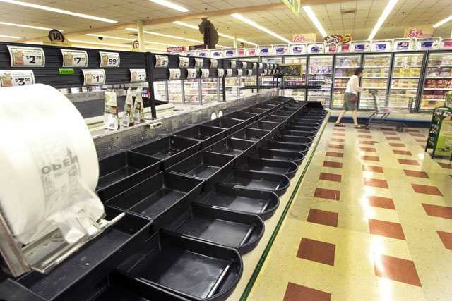 A customer walks by the empty produce isle at the Market Basket supermarket chain Thursday July 24, 2014, in Concord, N.H.