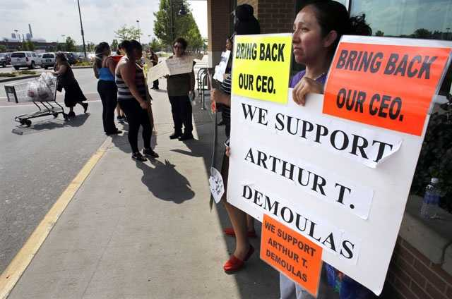 In this July 22, 2014 file photo ,demonstrators display placards outside a Market Basket supermarket in Chelsea, Mass.
