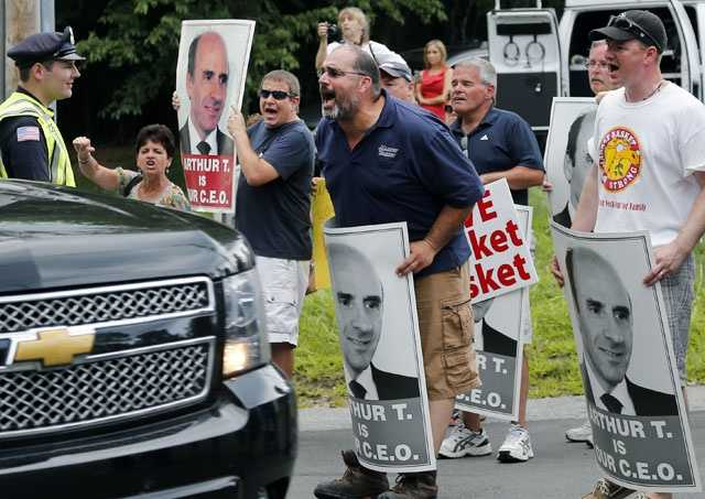 "Protesters holding ""Arthur T"" signs taunt an occupant of a car driving into a Market Basket Supermarket job fair in Andover, Mass., Monday, Aug. 4, 2014."