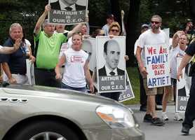 """Protesters holding """"Arthur T"""" signs taunt an occupant of a car driving into a Market Basket Supermarket job fair in Andover, Mass., Monday, Aug. 4, 2014."""