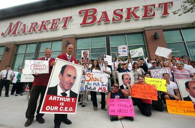 "Market Basket assistant managers Mike Forsyth, left, and John Surprenant, second from left, hold signs while posing with employees in Haverhill, Mass., Thursday, July 24, 2014, in a show of support for ""Artie T."" Arthur T. Demoulas, the former chief executive of the Market Basket supermarket chain."