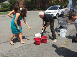 Emily and Cindy monitor as Randy scoops the ice into the buckets. Is he adding more to their buckets?