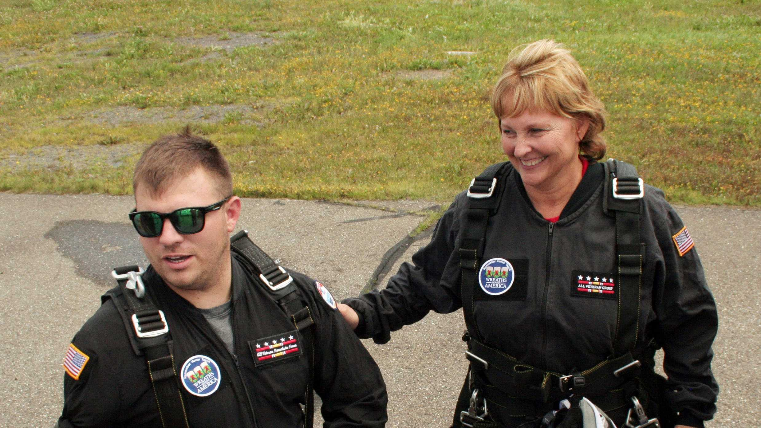 In this photo provided by the All Veterans Group, U.S. Army Staff Sgt. Travis Mills, left, walks with Maine's first lady Ann LePage prior to their parachute jump over Fort Kent, Maine, Saturday, Aug. 9, 2014.