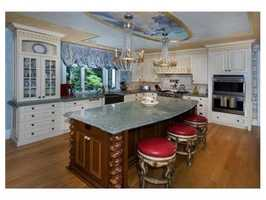 A chefs kitchen with custom cabinetry and a large eating area.