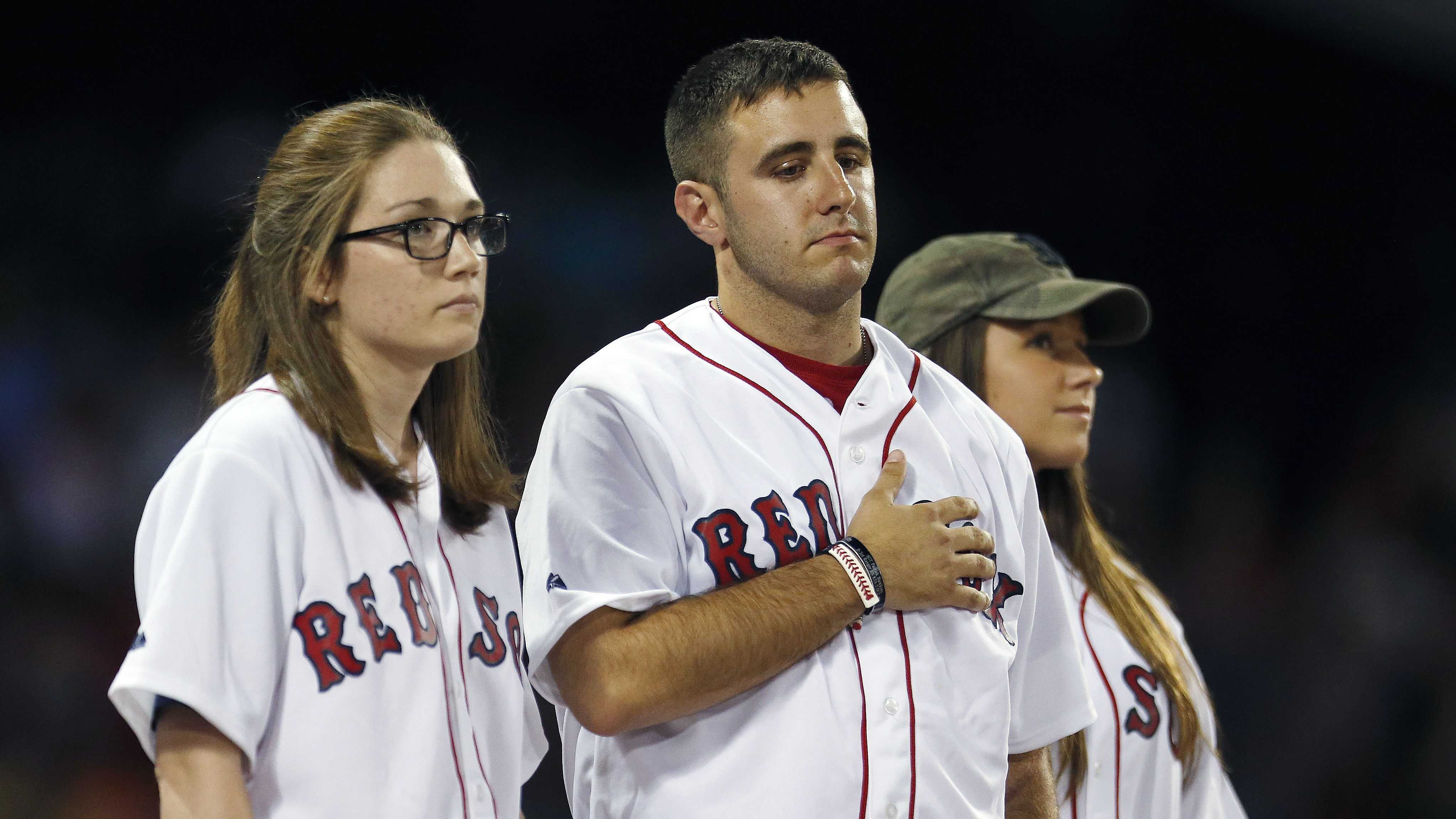 The family of Maj. Gen. Harold Greene, from left, daughter-in-law Kasandra, son Matthew and daughter Amelia, is honored during the fifth inning of a baseball game between the Boston Red Sox and the Houston Astros in Boston, Saturday, Aug. 16, 2014.