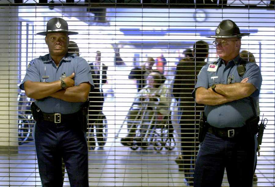 Two Massachusetts State Police troopers stand in front of the closed entrance to American Airlines gate area as passengers are evacuated, rear, at Logan International Airport in Boston, Tuesday, Sept. 11, 2001.