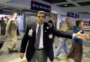 A Logan Airport security guard gestures as passengers are evacuated from the gate area of American Airlines Tuesday, Sept. 11, 2001, in Boston.