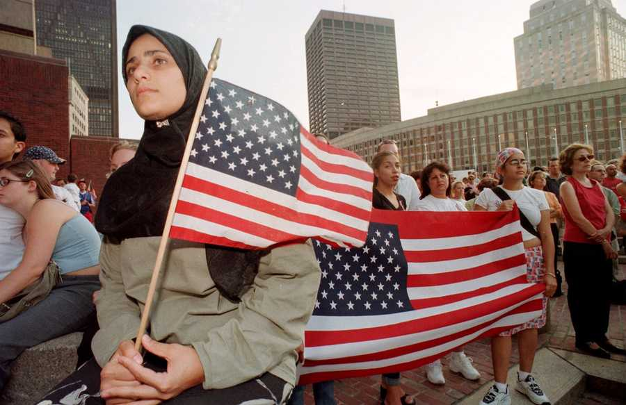 Hoda Elsherkawi of Cambridge, Mass., who works for the Islamic Society of Boston, holds a flag while listening to a prayer during an interfaith vigil of prayer and solidarity at Boston City Hall, Thursday, Sept. 13, 2001, in Boston. Jewish, Christian, Muslim and other religious leaders joined thousands of participants in the prayer vigil for victims of Tuesday's fatal terrorist hijackings.