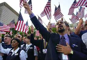 American Airlines service representative Luis Barbosa holds his hand on his heart as he and others from American and United Airlines participate in an interfaith prayer vigil in Boston Thursday, Sept. 13, 2001 to honor and remember those who died in Tuesday's terrorist attacks on Washington and New York.