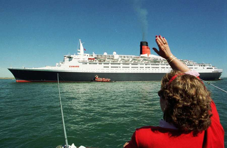 Judy Murphy, of Hingham, Mass., waves at the luxury liner Queen Elizabeth 2 as it steams into Boston Harbor Sunday, Sept.16, 2001. The QE2 left England Monday, the day before the World Trade Center attack, headed for New York, and was later diverted to Boston.