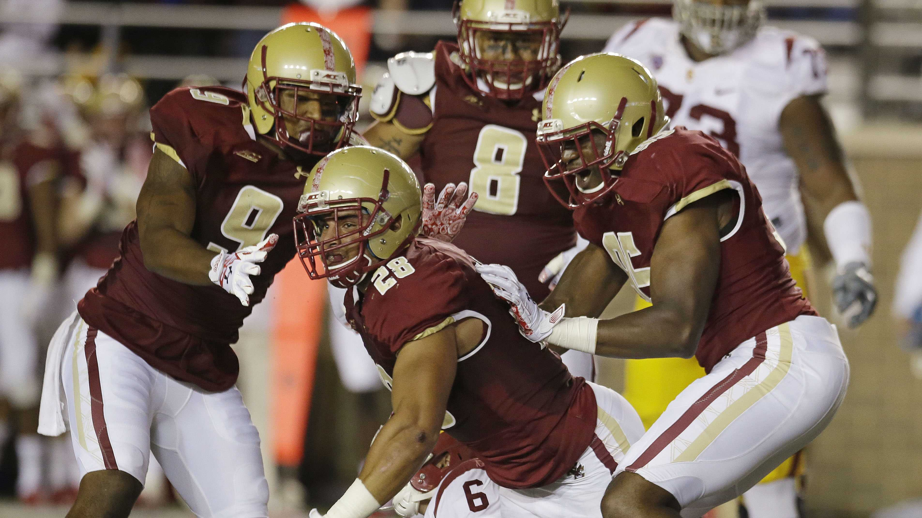Boston College linebacker Matt Milano (28) is surrounded by celebrating teammates&#x3B; defensive back Dominique Williams (9), defensive lineman Harold Landry (8) and defensive lineman Brian Mihalik (99) after Milano sacked Southern California quarterback Cody Kessler (6) during the second half of their NCAA college football game Saturday, Sept. 13, 2014 in Boston. Boston College defeated USC 37-31.