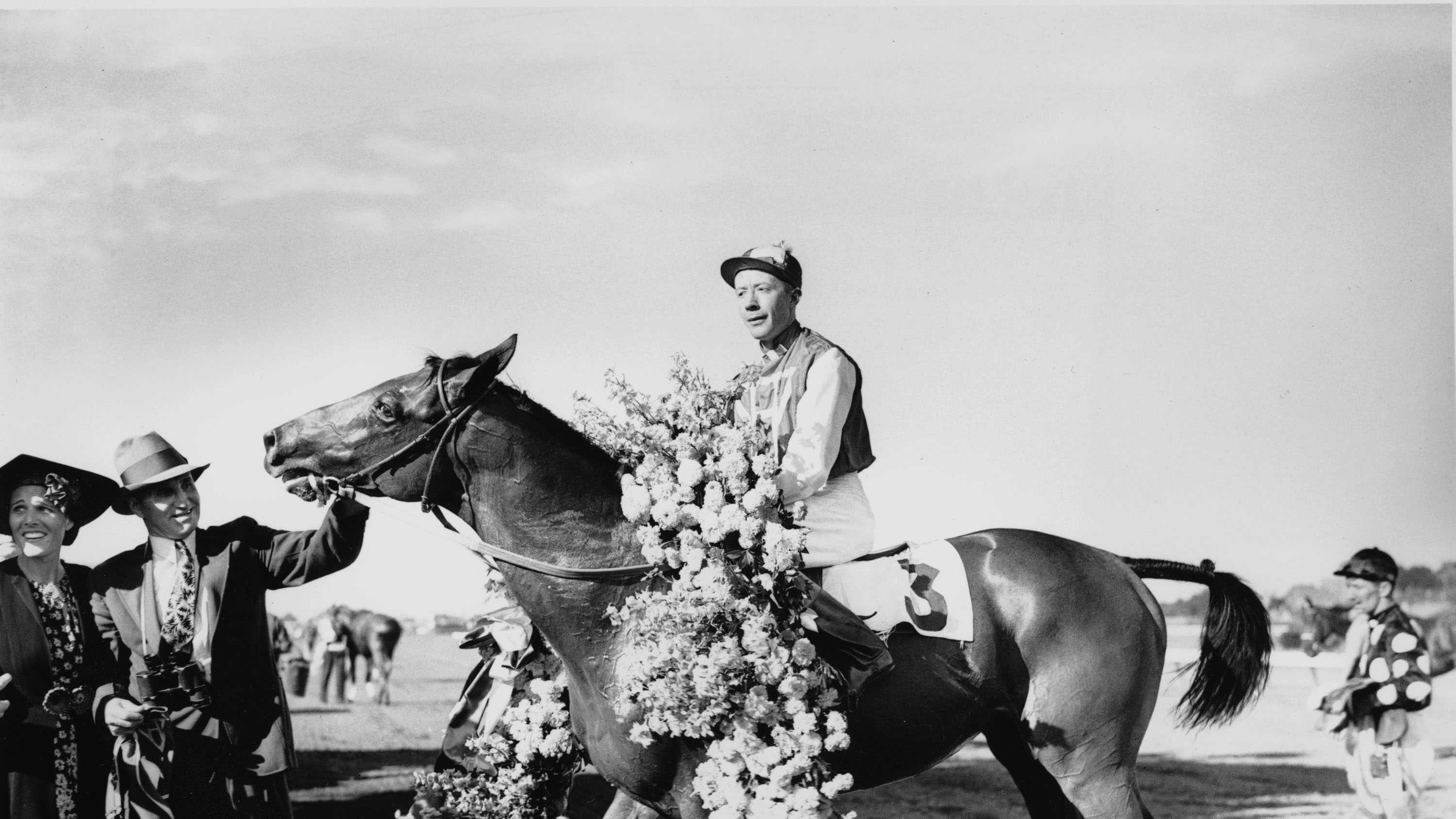 "Seabiscuit, wearing the victory flower garland, is shown with jockey Johnny ""Red"" Pollard after winning the $51,780 Massachusetts Handicap at Suffolk Downs on Aug. 7, 1937."