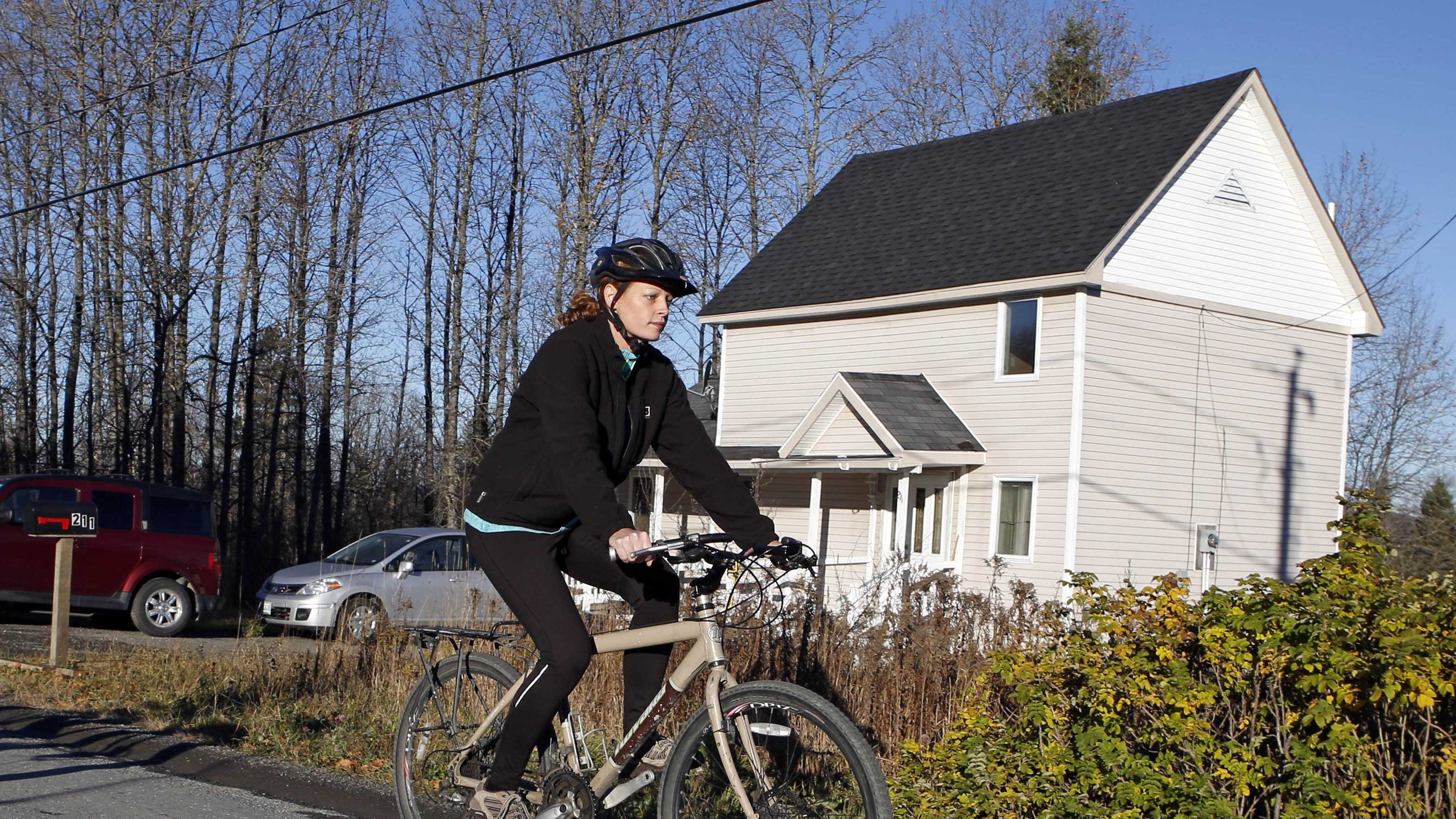 Nurse Kaci Hickox rides away from the home she is staying in on a rural road in Fort Kent, Maine, to take a bike ride, Thursday, Oct. 30, 2014. Hickox went on an hour-long ride with her boyfriend Ted Wilbur, followed by state police who were monitoring her movements and public interactions.