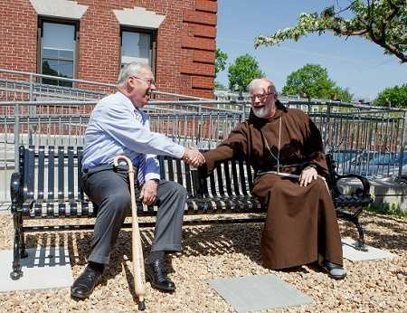 Cardinal Sean O'Malley greets former Boston Mayor Thomas Menino during a ceremony to dedicate a bench in honor of the former mayor outside Catholic Charities' Teen Center at St. Peter's in Dorchester May 12, 2014.