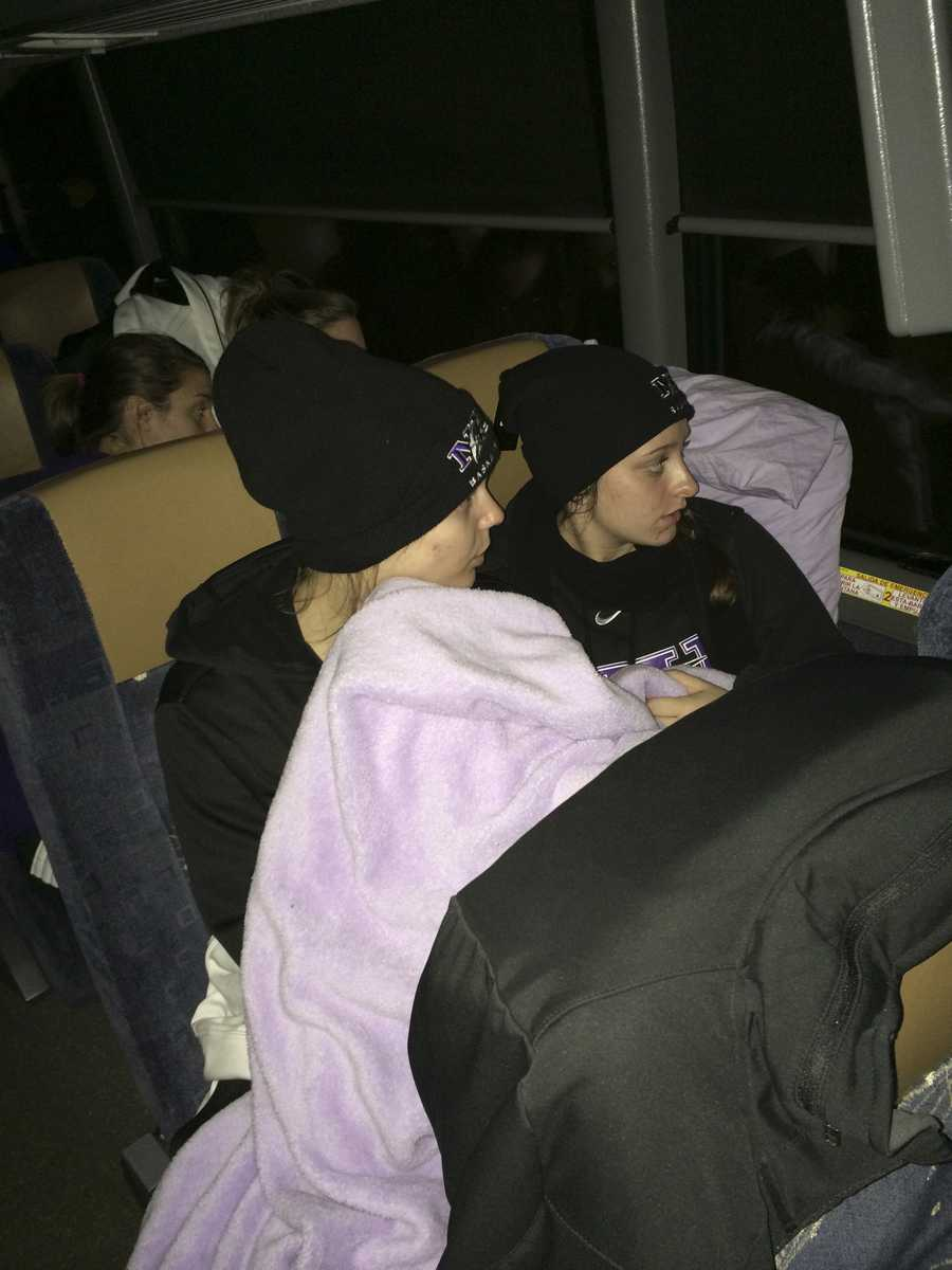 In this photo provided by Niagara's Tiffany Corselli, teammates Gabby Baldasare and Jamie Sherburne huddle under a blanket while stuck on a bus near Buffalo, N.Y., Tuesday, Nov. 18, 2014. The NCAA college basketball team has been stuck on the highway in its bus for nearly 24 hours because of a winter storm that dumped about 4 feet of snow around Buffalo.