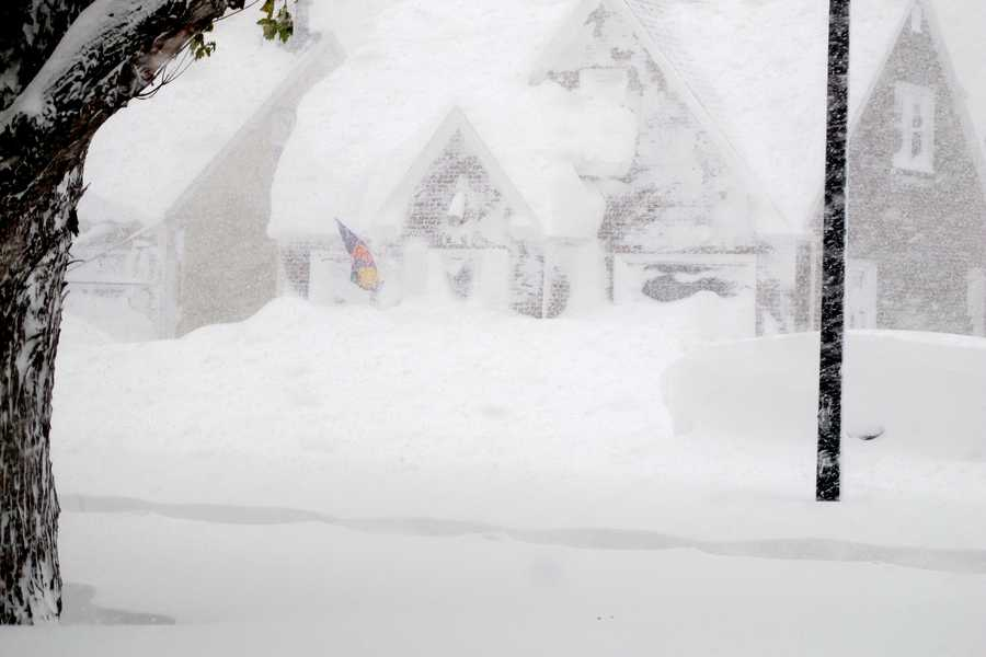 A house is obscured by wind-blown, lake-effect snow on Tuesday, Nov. 18, 2014 in Buffalo, N.Y. Parts of New York measured the season's first big snowfall in feet, rather than inches, as 3 feet of lake-effect snow blanketed the Buffalo area. The Thruway Authority said white-out conditions caused by wind gusts of more than 30 mph forced the closure of Interstate 90 in both directions from the Rochester area to Ripley, on the Pennsylvania border 60 miles southwest of Buffalo.