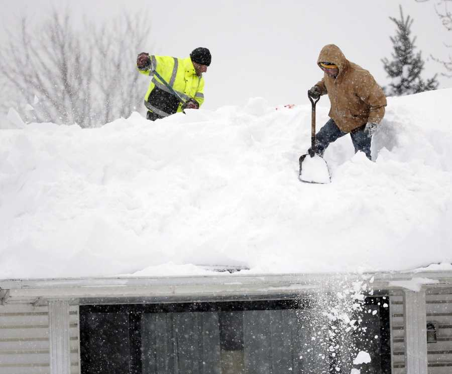 Mark Settlemyer, left, gets help clearing snow from the roof of his mother's house from Ken Wesley on Wednesday, Nov. 19, 2014, in Lancaster, N.Y.