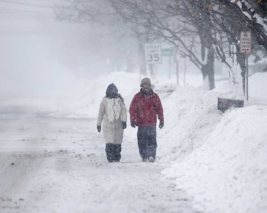 Pedestrians walk along a snow-covered street on Wednesday, Nov. 19, 2014, in Lancaster, N.Y.
