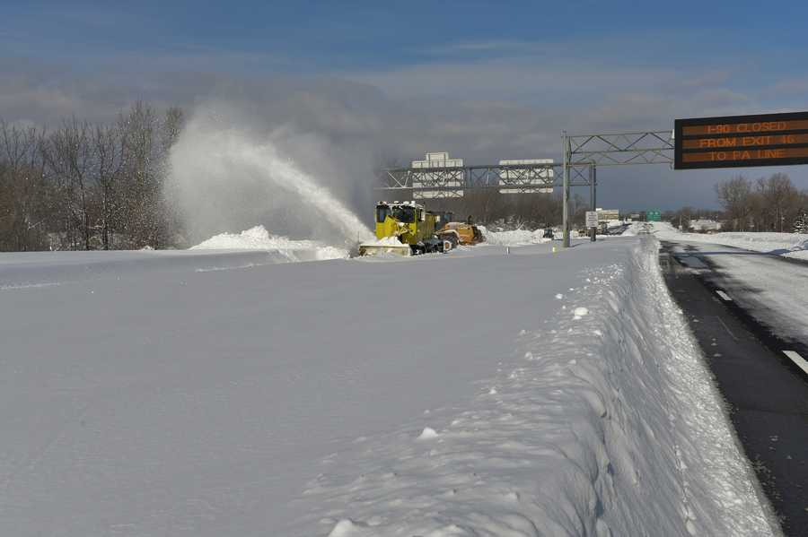 A snow crew works at clearing away five to six feet of snow that fell on the New York State Thruway south of Buffalo.